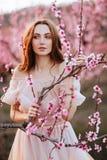 Chica joven hermosa debajo del árbol rosado floreciente imagen de archivo