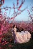 Chica joven hermosa debajo del árbol rosado floreciente imagen de archivo libre de regalías