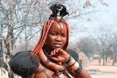 Chica joven hermosa del himba con el peinado, los anillos, el collar y las pulseras nacionales en fondo tradicional del pueblo de fotografía de archivo libre de regalías
