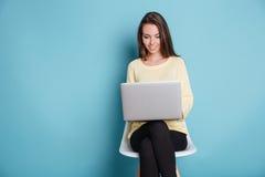 Chica joven hermosa elegante que usa el ordenador portátil sobre fondo azul Fotos de archivo libres de regalías