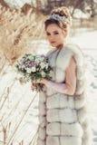Chica joven hermosa en abrigo de invierno con la corona y el ramo Foto de archivo