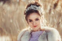 Chica joven hermosa en abrigo de invierno con la corona y el ramo Fotos de archivo libres de regalías