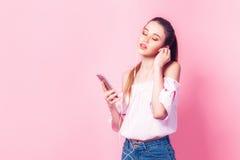 Chica joven hermosa en auriculares que escucha la música con cierre Foto de archivo