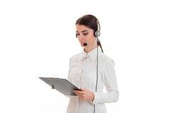 Chica joven hermosa en auriculares y una camisa blanca que sostiene una tableta Imagen de archivo libre de regalías