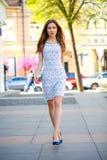 Chica joven hermosa en calle del verano del vestido que camina blanco Fotos de archivo