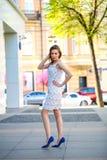 Chica joven hermosa en calle del verano del vestido que camina blanco Imagen de archivo
