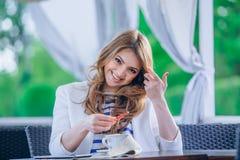 Chica joven hermosa en el café al aire libre a de lectura Imagenes de archivo