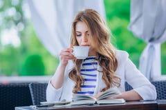 Chica joven hermosa en el café al aire libre a de lectura Fotos de archivo libres de regalías