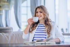 Chica joven hermosa en el café al aire libre a de lectura Foto de archivo libre de regalías