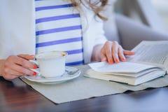 Chica joven hermosa en el café al aire libre a de lectura Imágenes de archivo libres de regalías
