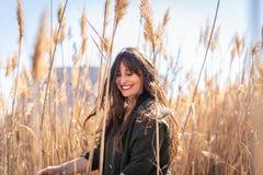 Chica joven hermosa en el campo y la sensación de la naturaleza imagen de archivo