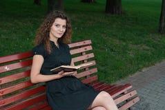 Chica joven hermosa en el libro de lectura de la tarde al aire libre imagenes de archivo