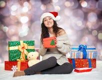 Chica joven hermosa en el sombrero con las cajas de regalo, bokeh colorido de santa del día de fiesta Imágenes de archivo libres de regalías