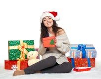Chica joven hermosa en el sombrero de santa con las cajas de regalo, en el fondo blanco Imágenes de archivo libres de regalías