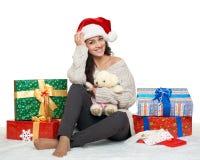 Chica joven hermosa en el sombrero de santa con las cajas del juguete y de regalo del oso de peluche, fondo blanco Fotografía de archivo libre de regalías
