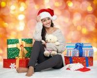 Chica joven hermosa en el sombrero de santa con las cajas del juguete y de regalo del oso de peluche, fondo colorido del bokeh Foto de archivo