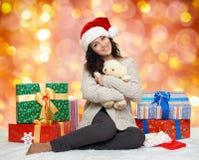 Chica joven hermosa en el sombrero de santa con las cajas del juguete y de regalo del oso de peluche, fondo colorido del bokeh Fotografía de archivo