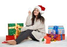 Chica joven hermosa en el sombrero de santa con las cajas grandes del juguete y de regalo del copo de nieve, fondo blanco Imagenes de archivo