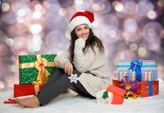 Chica joven hermosa en el sombrero de santa con las cajas grandes del juguete y de regalo del copo de nieve, fondo colorido del b Fotos de archivo libres de regalías