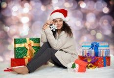 Chica joven hermosa en el sombrero de santa con las cajas grandes del juguete y de regalo del copo de nieve, fondo colorido del b Fotografía de archivo