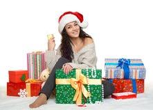 Chica joven hermosa en el sombrero de santa con un vidrio de cajas del champán y de regalo Imágenes de archivo libres de regalías