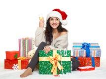 Chica joven hermosa en el sombrero de santa con un vidrio de cajas del champán y de regalo Fotos de archivo libres de regalías