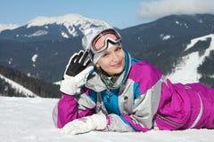 Chica joven hermosa en el traje de esquí que miente en la nieve Imagen de archivo libre de regalías
