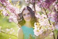Chica joven hermosa en flores Foto de archivo libre de regalías
