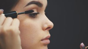 Chica joven hermosa en fondo negro El uso de la res muerta para las pestañas, belleza facial, piel pura, compone conceptos almacen de video