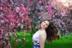 Chica joven hermosa en jardín de flores de la primavera Imagenes de archivo