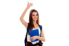 Chica joven hermosa en la camisa blanca y con una cartera de sonrisas y aumentada su brazo para arriba Imagen de archivo