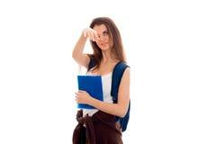 Chica joven hermosa en la camisa blanca y con una cartera que sostiene una carpeta azul y que cubre su cara Foto de archivo libre de regalías