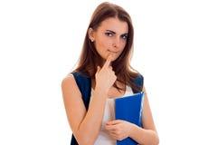Chica joven hermosa en la camisa blanca y con una cartera y frustrado en sostener una carpeta azul Fotos de archivo libres de regalías