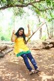 Chica joven hermosa en la diversión amarilla de la alineada en el oscilación Fotos de archivo libres de regalías