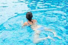 Chica joven hermosa en las gafas de sol que flotan en la piscina Foto de archivo libre de regalías