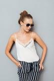 Chica joven hermosa en las gafas de sol que presentan y que miran lejos Imagen de archivo libre de regalías