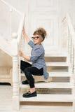 Chica joven hermosa en los vidrios que se sientan en las escaleras del cuarto brillante Fotografía de archivo libre de regalías