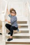 Chica joven hermosa en los vidrios que se sientan en las escaleras del cuarto brillante Imagenes de archivo