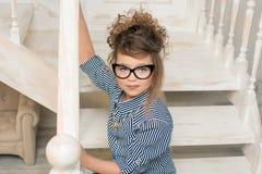 Chica joven hermosa en los vidrios que se sientan en las escaleras del cuarto brillante Foto de archivo libre de regalías