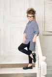 Chica joven hermosa en los vidrios que se sientan en las escaleras del cuarto brillante Fotos de archivo