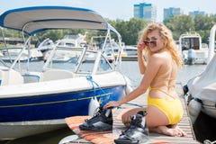 Chica joven hermosa en un bañador amarillo, sentándose cerca de BO foto de archivo