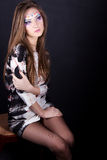 Chica joven hermosa en un maquillaje de la fantasía que se sienta en el estudio en una silla en un fondo negro Fotos de archivo libres de regalías