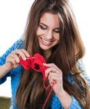 Chica joven hermosa en un suéter azul que se coloca con una bola roja del hilado y que hace punto una bufanda y un perro de Pomer Imágenes de archivo libres de regalías