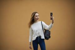 Chica joven hermosa en un suéter ligero en un fondo amarillo de la pared Imágenes de archivo libres de regalías