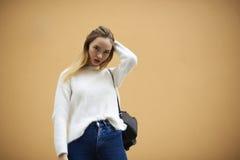 Chica joven hermosa en un suéter ligero en un fondo amarillo de la pared Foto de archivo libre de regalías