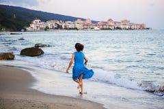 Chica joven hermosa en un vestido azul que corre a lo largo de la playa, borrosa fotografía de archivo