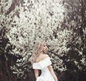 Chica joven hermosa en un vestido blanco hermoso cerca de un árbol floreciente Imagen de archivo
