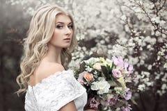 Chica joven hermosa en un vestido blanco hermoso con un ramo cerca de un árbol floreciente Foto de archivo
