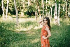 Chica joven hermosa en un vestido rojo del verano en un parque imagenes de archivo