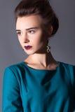 Chica joven hermosa en un vestido y un maquillaje brillante Foto de archivo